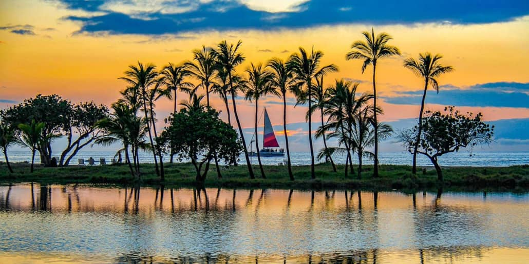 Sail Boat at Sunset with Palms Big Island shutterstock