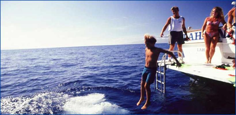 Boy jumping in water from snorkel boat