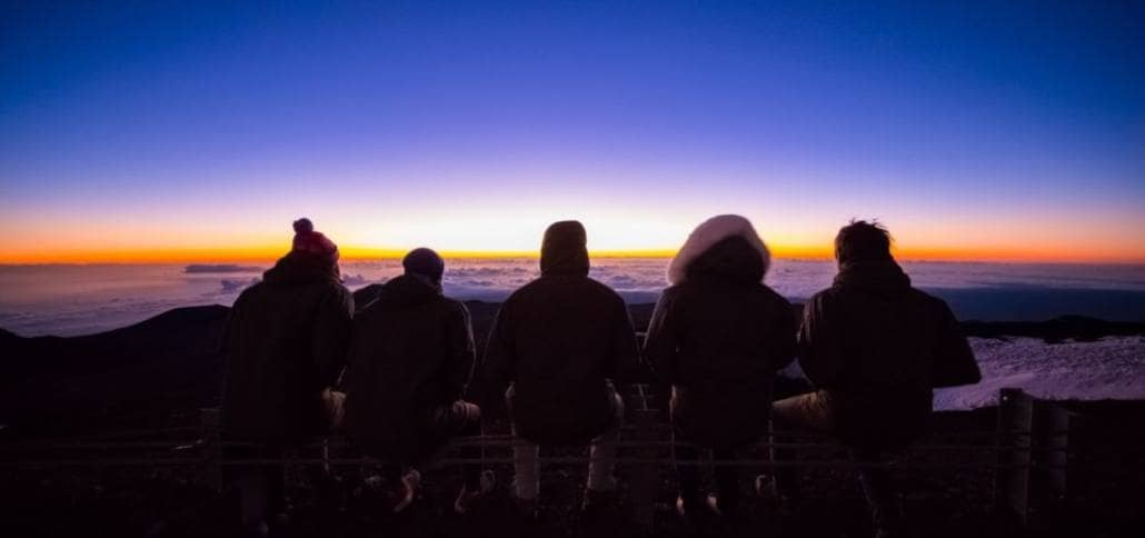 5 people sitting on bench watching sunrise