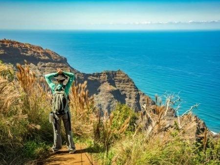 Hiking Visitor at end of the Awa Awapuhi trail Overlooking Na Pali Coast Kauai shutterstock